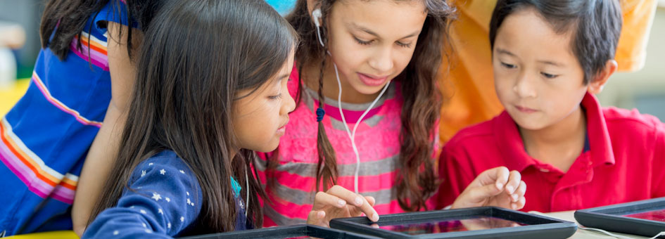 A girl wearing headphones touches the screen of a tablet. 4 children around her look at the screen.