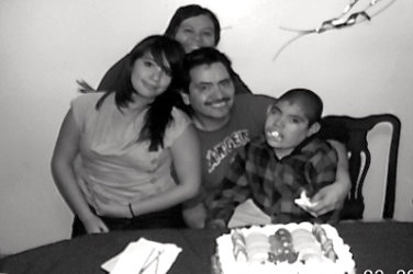 Myrna, her daugther Deloris, her husband Juan and her son Norman in front of a cream covered cake.