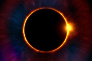 Eclipse. The dark moon covers the sun leaving only visible a ring of fire.