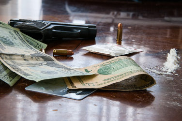 Over a table: a gun, 3 bullets, a bag of cocaine and several dollars spread around
