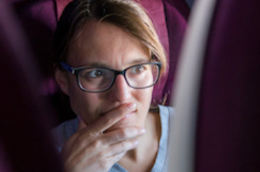 Airplane, Woman with glasses looks forward to the back of a seat in front of her