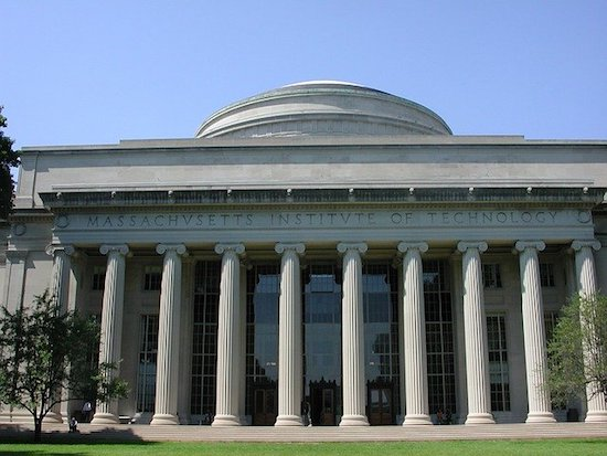 Facade of gray building with a colonnade of 10 round 30 feet tall columns. Along the facade, over the columns, carved is the phrase