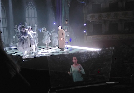 Scene of The Addams Family in the theater. Like floating in the air, on the transparent lectern the sign language interpreter is seen. The interpreter raises her left arm and has her right arm folded against her body.