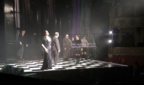 Theater. The Addams Family scene. Subtitles appear on a transparent lectern.