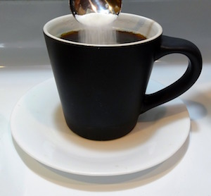 A cup of black coffee. White sugar falls in the coffee from a spoon.