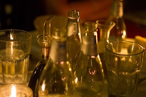 Glasses and bottles dimly lit by candles