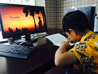 A boy writes on a notebook in front of a screen