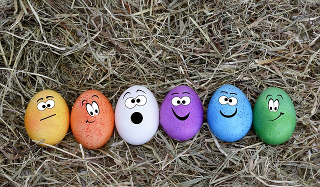 On dead grass, row of colored Easter eggs with faces painted