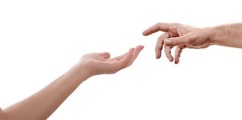 The forearm of a woman extends with the palm of her hand facing up. The hand of a man, with the palm facing down and the index finger slightly bended, approaches the woman's hand.