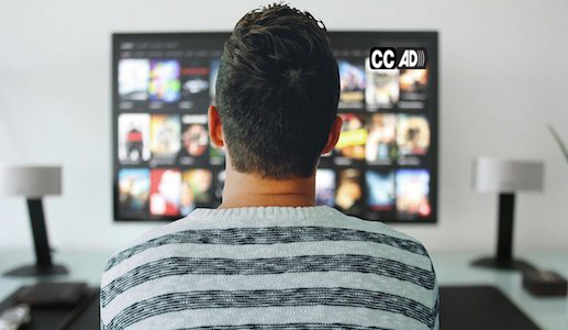 A man seated in front of a TV. On the upper right corner of the TV screen appear the captioning and audio description icons.
