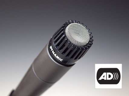 A microphone pointing up and to the right. The letters AD that indicate audio description appear on the the bottom right.