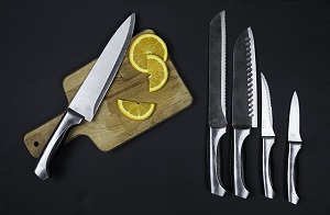 Set of 5 stainless steel knives over a black background. One of the knives rest on a wood cutting board, next to 2 orange slices.