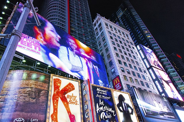 At night, Times Square billboards of the Broadway shows: On Your Feet, Kinky Boots, and An American in Paris